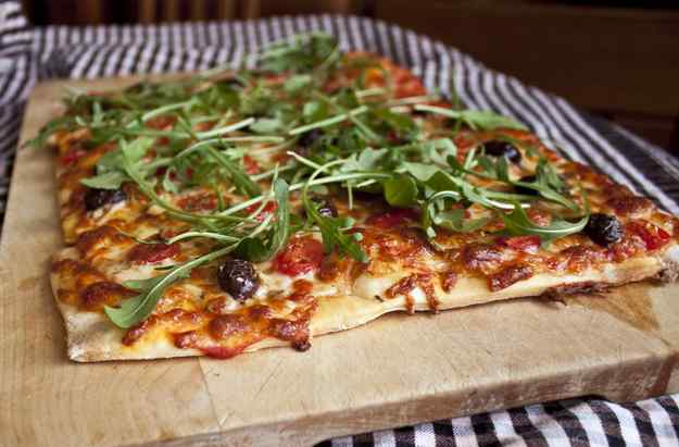 Pizza de tomàquets, olives negres i ruca